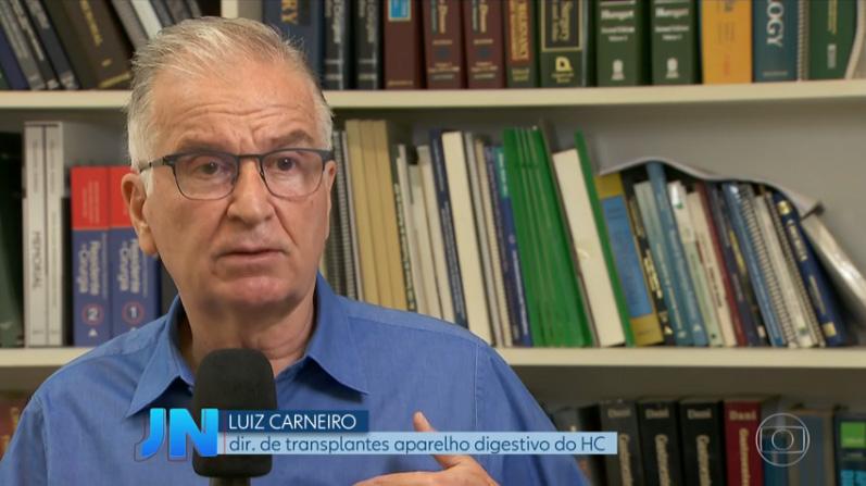 Ao fundo da imagem, há o Prof. Dr. Luiz Carneiro de frente para a câmera com um microfone na mão.