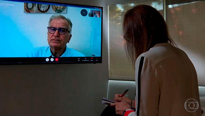 A imagem mostra uma mulher de costas para a câmera, olhando para uma tv onde está transmitindo a câmera do Prof. Dr. Luiz Carneiro.