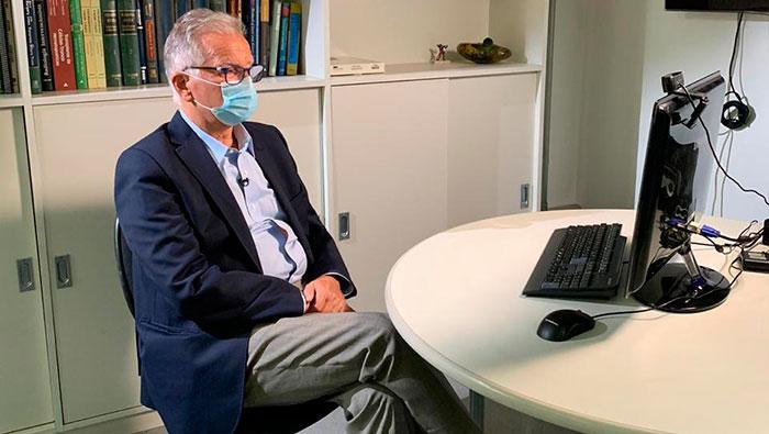 A imagem mostra o Prof. Dr. Luiz Carneiro sentado na frente de um computador.