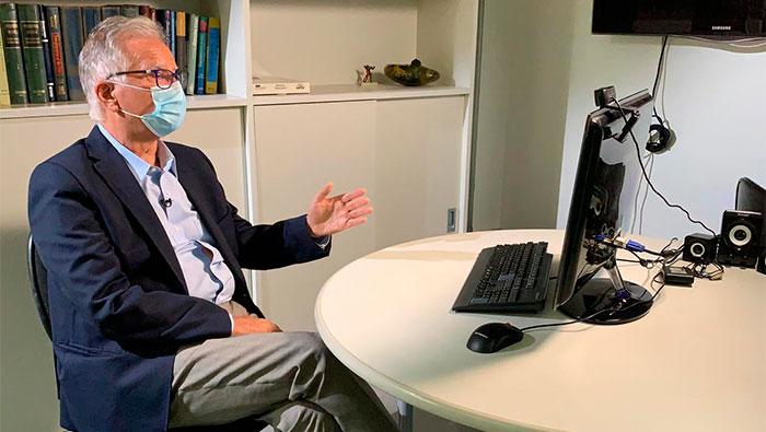 A imagem mostra o Prof. Dr. Luiz Carneiro gesticulando com as mãos, na frente de um computador.