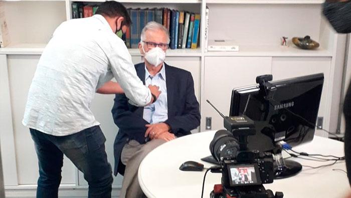 A imagem mostra um homem arrumando a roupa do Prof. Dr. Luiz Carneiro para a gravação.
