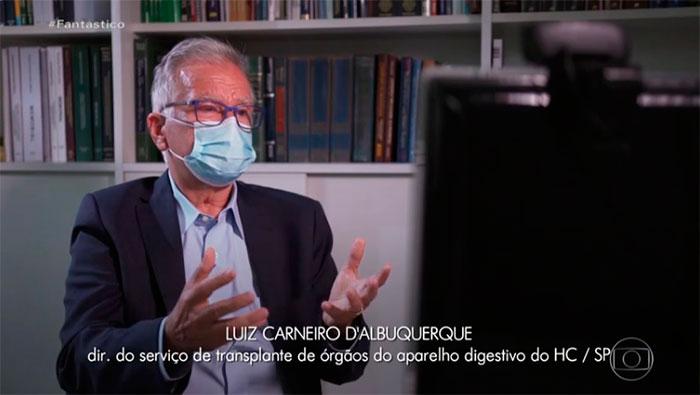 A imagem mostra o Prof. Dr. Luiz Carneiro, sentando em uma cadeira, gesticulando com as mãos para uma câmera.