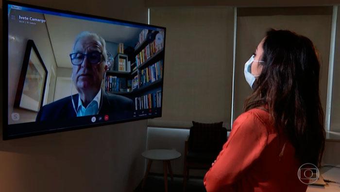 A imagem mostra uma mulher de costas para a câmera, na diagonal, olhando para um televisão. Nesta televisão, há uma chamada de vídeo com o Prof. Dr. Luiz Carneiro.
